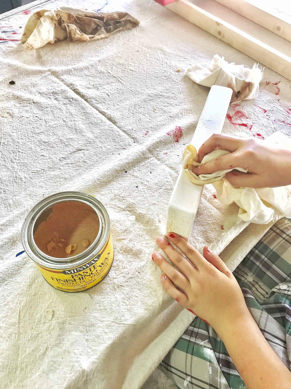 Young girl waxing a piece of a Jenga block