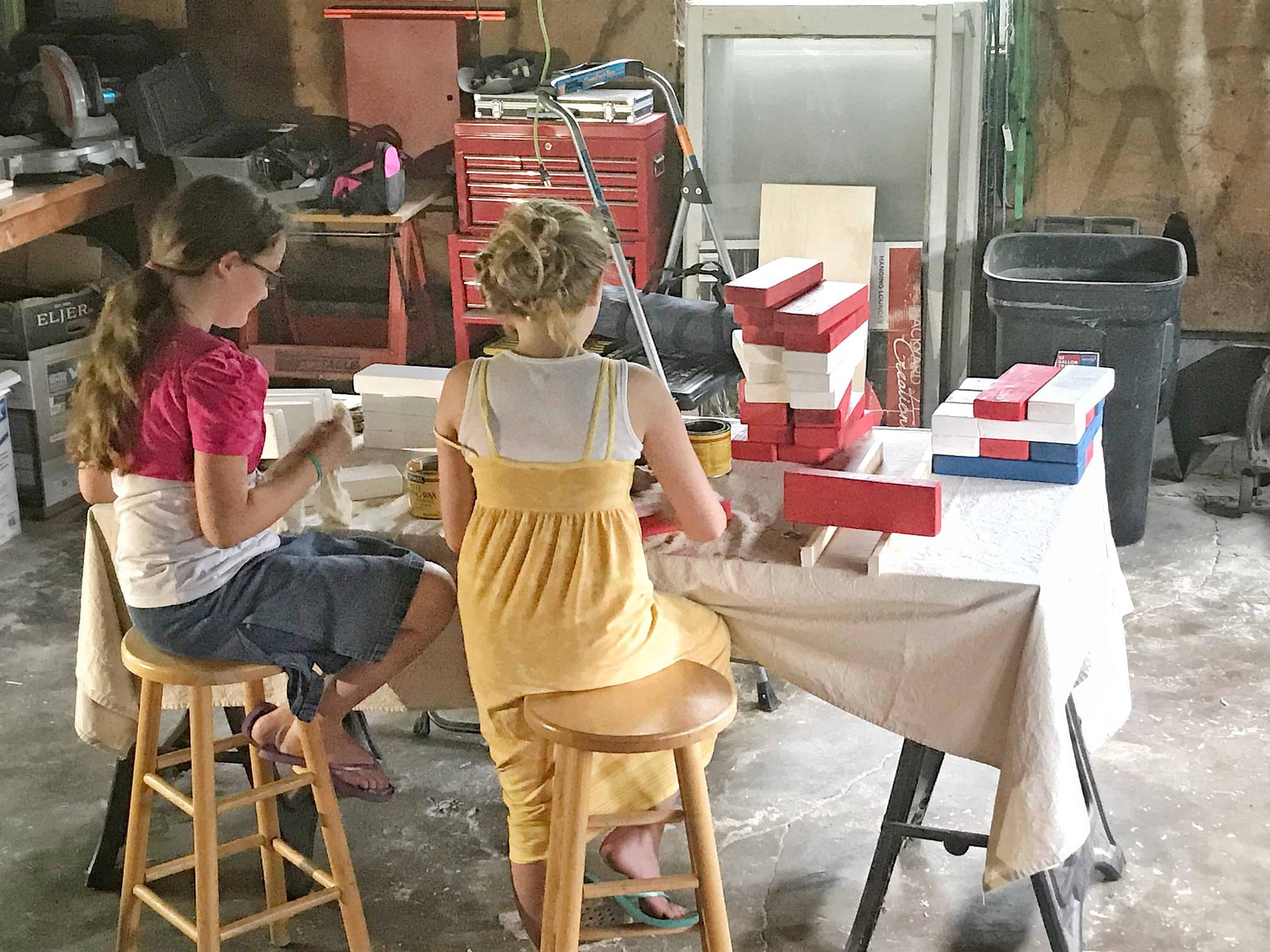 girls working on waxing a Jenga game set
