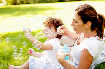 mom and young child smiling and blowing bubbles together
