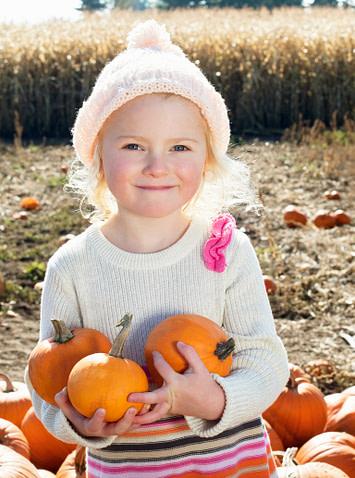 little girls holding mini pumpkins in a pumpkin patch