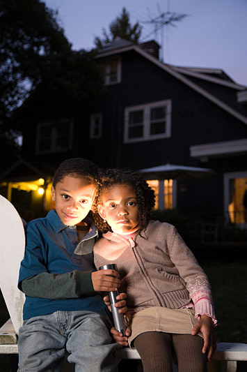brother and sister with flashlight telling ghost stories, family-friendly Halloween traditions
