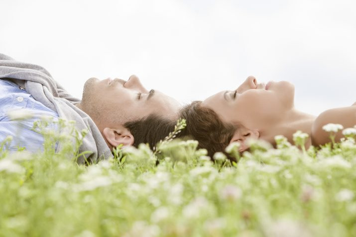 couple laying on the grass resting in emotional intimacy