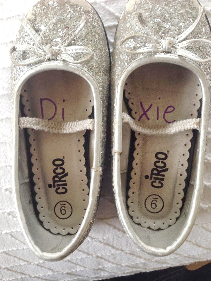 a pair of little girl's shoes with half her name in one shoe and the other half of her name in the other shoe to show which shoe goes on the right foot.